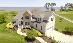 Paradise at The Point! This luxurious 4 bedroom 4.5 bath custom built estate home is located on the pristine greens of Rum Pointe Golf Course with panoramic views of Sinepuxent Bay and Assateague Island.  Spacious at 4,221SF, this magnificent waterfront residence graced by soaring ceilings and wall-to-wall windows is a haven for gazing at water views from multiple vantage points. The grand foyer opens to a formal living room, dining room, great room with wet bar for easy entertaining. First floor master bedroom boasts water views with private access to the rear porch and deck. A generous bonus room on the 2nd story is the perfect space for a billiard room, playroom, media room or home gym! A private fishing/crabbing pier is available for the exclusive use of the nine Rum Point homeowners.