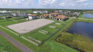 This exquisite Grand Prix Village South farm features a 20-stall barn with 2 large tack & feed rooms, 4 wash stalls, laundry room, kitchen area, 2 storage rooms and 1 full bathroom. There is a magnificent 1 bedroom owner's apartment on the second level with a spacious balcony overlooking the  210' x 120' riding arena and 5 paddocks. Property also has a separate building with a 3 car garage/storage and a 2 bedroom grooms apartment on the upper level. San Remo Farm is absolutely stunning!