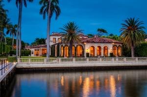 Spectacular Maurice Fatio designed Mediterranean Estate on the Intracoastal with gorgeous architectural detailing. With 17,000+/- total sq. ft. and 7BR/9.4BA, this stunning estate is perfect for entertaining. Elegant foyer with wrought iron spiral staircase leads to oversized reception room with 20+ ft. ceilings. Elaborate columned dining room seating 30, features beautiful fireplace and stunning coffered ceiling. Highlights include 60 ft. +/- formal living room, soaring ceilings, striking plaster moldings, gorgeous library, gym, and breakfast room with built-in grill. Formal loggia frames romantic sunsets overlooking the water. Gated entryway opens to beautiful carriage house, welcoming motorcourt, and 4 car garage. Meticulously manicured grounds features pool, beautiful fountains, dock,