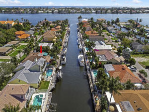 Direct Ocean Access location with a private dock makes that is a must see for boaters. Imagine having your dream boat with 75 of dock space in the back of your dream home. The deep canal will accommodate a large boat. The backyard is perfect to entertain with a spacious pool, plenty of room for areas to enjoy the sun and shade. Imagine dining outdoors or floating in the pool with a cool drink. The home has 3 bedrooms and a welcoming open layout. You will like the charm of the unique fireplace, plantation shutters, crown molding and wood ceiling. There is a permitted a/c 13 x 10 playroom in the garage.  The a/c, water heater, pool marcite, and pool pump are newer