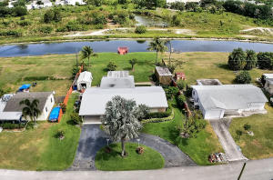 Bring your water toys to boaters paradise. Beautiful home with dock on canal between Lake Clarke Shores and Lake Osbourne. This open floor plan home was updated in 2004-custom tile baths, ceramic tile flooring throughout, and 2018-white kitchen cabinets/black granite, metal roof, electric., impact windows (all but 2), generator. Large formal living room can convert back to 3rd and 4th bedrooms (add 2 walls.) The French doors of great room lead to the covered porch. 2nd door leads to  patio. This waterfront oasis is the perfect home for entertaining and has room for a pool! Home boasts security system, speaker system, 4 zone auto sprinklers, carport, fruit trees, shed and orchid house for extra storage and plantings. NO HOA and SUPER LOW TAXES!! Convenient to shops,schools,I95