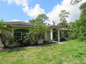 This diamond in the rough is a blank canvas for anyone with creativity . Make this house a home.  The home sits on 1.54 acres on a dead end street with a drainage canal on the east side of the home and on the south side of the home.  There is a large master bedroom with walk in closet and glass sliders to access the backyard. Both bathrooms have shower/tub combo. Split floor plan. Large living room with fireplace . Buyer to verify exposure all measurements are approximate .