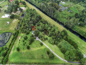 This property is one of a kind for 7.33 acres at the end of the street with paved roads. This fully fenced Loxahatchee property is a dream come true. You will love living in Wildwood with all of the room to have pets, horses and privacy. The property abuts to the L8 canal and has easy access to the equestrian trails. This is an amazing value and will sell quickly. The home was completely redone in 2015 and has a steel structure with hardie board siding. Inside you will appreciate the open design and split floor plan. The property could easily be a 3 bedroom or you can build another structure on the property as well. The main level is a huge 1440 sf garage, workshop, 324 sf storage area for equipment or so much more. On your mark, get set, come & see it. Bring your highest & best offer.