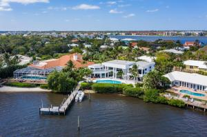 This masterfully designed modern estate is the perfect property for living the waterfront lifestyle! Easily enjoy your yacht, jets skis, and all water sports from your private dock with easy access to the Boynton Inlet. Each room in this 5 bedroom, 5.5 bathroom home offers spectacular views of the intracoastal waterway. The spacious, open floor plan is bathed in natural light that pours in from the running walls of glass that blends the outside with the inside and brings the entire home to life. The homes covered patio features an outdoor kitchen and lakeside pool and spa that is accessible through the impact glass sliders in the living room and kitchen.  An oversized master bedroom provides the ultimate retreat with a sitting room, marble bathroom, and generous closet space.