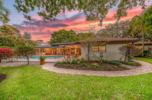 Nestled by majestic oak trees on one of the largest lots in Historic Old Floresta sits this renovated 4 bedroom plus office pool home basking in an abundance of natural light. Combining both indoor and outdoor living with warm textural elements this timeless East Boca jewel features 4,426 total square feet all on one level. Throughout this open and airy floor plan you will find porcelain tile in living areas, a new gourmet kitchen complete with center island, granite counter tops, Viking range, and a built-in Miele coffee system. The master suite set amongst the manicured gardens has been graciously expanded to include a large walk-in closet and full bath adorned with Italian marble, soaking tub and glass encased shower. Enjoy quiet moments or easy entertaining all year long by the heated