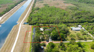 This Jupiter Farms single family home sits on 1.37 acres, perfectly located on a quiet and paved road with Preserve views on south side of the property. 5 bedroom, 3 bath, 1 powder room, a/c Kennel and separate workshop. Paver brick walkway to front entrance. Foyer leads to Living room featuring a stone fireplace and vaulted ceiling. Kitchen has wood cabinets and a breakfast nook. Formal dining room. Master bedroom is located on the first floor and features oversized master and linen closets. Master bath has separate soaking tub and shower.  Minutes from dining, shopping, entertainment and Jupiter beaches!