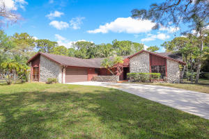 This 4 bedroom, 2 bath, 2-car garage home is located on a beautiful 1.2 acre lot on the corner of two paved roads in a very nice section of Palm Beach Country Estates. Features 2,480 square footage under air and 3,280sf total. Remodeled luxury master bathroom and large walk-in closet in master bedroom. Huge 27x21 living room. Stone fireplace and wood paneled ceiling in family room. Stainless steel appliances in kitchen. Vaulted ceilings. Split bedrooms. Large concrete driveway. Screened porch. Palm Beach Country Estates features city water available for hook-up at every property, no formal HOA restrictions, and is close to all area amenities including Abacoa, Alton Town Center, and beaches.