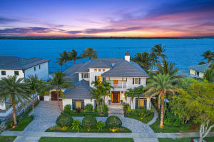 This waterfront estate designed by Randall Stofft and built by renowned builder Turtle Beach Construction is the definition of refined luxury living in one of the most desirable North Palm Beach neighborhoods. Stunning sunrises and sunsets over the wide water pour through oversized windows throughout the home, while its location across from MacArthur State Park offers nature views from all vantage points.  Immediately upon entering the grand two-story foyer, you will find an abundance of high-end features, such as the elegant Capiz shell chandelier, coffered ceilings, and custom millwork all of which add charm and sophistication to this magnificent home.  The welcoming foyer leads you directly into the bright airy living room with its exceptional wide water views, grand fireplace and