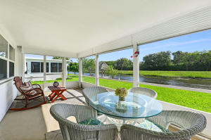 Waterfront Delight...Updated 2br/2ba with both full Fla room and screened porch. Roof & A/C replaced 2016. Impact windows front and back only,  Screen porch has roll-ups and accordion shutter. 20 neutral porcelein tile thru-out.  Kitchen cabinetry replaced, recessed lighting, extra cabinetry in kitchen and Fla. room. Hurricane rated front door and garage door. Both  baths vanities and electric fixtures replaced.  Shower in Master bath retiled.  Electric Service Panel & wiring all replaced. Decorative drive. Beautiful water views and boating to major lakes.. Close to shopping, restaurants and minutes to ocean beaches. Paid up recreation lease in full. Free 18Hole golf Par 3. Three heated pools, 3 clubhouses, fitness center. A Must see.Bedroom pictures virtually staged with furniture.