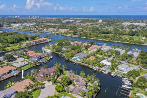 A boaters dream home with 100ft of waterfrontage with direct access to South Floridas renowned Intracoastal Waterway! This spacious 4BR/4BA home offers a split bedroom layout with a separate office and other desirable features and upgrades throughout such as a spacious kitchen with granite countertops, stainless steel appliances and a breakfast nook, a huge family room with French doors leading to the patio and stunning views of the water, a wet bar area with mini fridge and wine cooler, and an incredible red brick paved patio area with a built-in summer kitchen, cypress ceilings, TONS of room for relaxing and entertaining, and a spa-like pool with hot tub. Then step down to find your private 100ft dock with 14,000 lb boat lift that can fit up to an 85ft boat.
