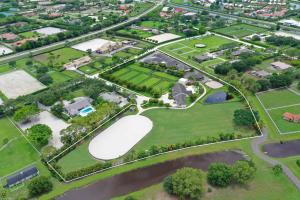Less than a mile hack to WEF with direct bridle path access!  Saddle Trail Park green, lush, spacious & complete professionals equestrian compound on 2 lots totaling 6.2acres. Complete with ~105 x 230 newly done Bermuda grass riding field, ~115 x 215 oval Olympic all weather sub-irrigated riding arena, 24 stall barn built 2015, additional 6 stall barn with feed room/flex door and bathroom that could be a quarantine facility plus 5 bedroom, 3.1 bath w. pool staff home.  Rower and Rub bamboo wood stalls include Nelson Automatic Waters, and with solar tunnel lighting and a separate riders lounge with office and bar, youre sure to have it all. Property has direct access to bridle path straight into WEF. There is a 6-horse Kraft walker on site in addition to a storage building... SEE MORE