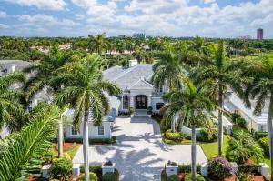 329 Royal Palm Way is a two-story estate appointed with grand views of the Royal Palm Yacht & Country Club Jack Nicklaus Signature golf course 1st fairway. The completely updated home features 4 bedroom suites (4th bedroom converted to a theater), 4 full and 1 half bath, and a spacious 5,548 split floor plan. A covered entry with glass and wrought iron detailed doors opens to a spectacular formal living room featuring two-story ceilings, a dramatic cast-stone fireplace, and see-through views of the pool. The updated gourmet kitchen has sleek and modern style complete with top-of-the-line SubZero and Wolf appliances, a large island with snack bar seating and waterfall edge, a temperature-controlled wine room, designer pendant lighting, and a coffee bar. The kitchen opens to the family room
