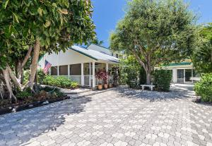 This lovely Key West style home & adorable guest cottage is located in the desirable community of Juno Beach between Pelican Lake & the Atlantic Ocean. This property, the 4th home west of the beautiful beaches of Juno, includes a short access to the ocean via a private road. The home & cottage are across the street & have views of Pelican Lake that includes a park for all ages, with swing sets, half basketball court, play structure, exercise equipment, a Bocce court & picnic tables. The primary residence was designed & has been meticulously maintained by the current owners. The great room includes the following attractive features: vaulted ceilings, propane fireplace, built-in bar & cabinet. The kitchen includes custom hardwood cabinets w/soft touch drawers, Corian countertops,  (Contd.)