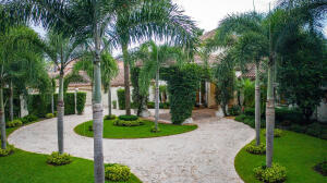 The Island, a private gated subdivision with only 12 custom homes with lake and golf course views is the jewel of Boca West Country Club.   Exceedingly private and beautifully landscaped this rarely available home boasts 7728 square feet of living space plus 5 garages.  Nestled on a .66 acre lot this stately home features 5 bedrooms, 7 and half baths, library, home theatre, wet bar, gym and elevator.  Drive up to the porte-cochere and enter the home though its gracious foyer, where the homes character, style, and quality are immediately apparent.  The 19 foot long foyer opens to a spectacular open-plan main living area withliving room, dining room, bespoke grand staircase and the most magnificent view of the backyard with lake and golf course views.