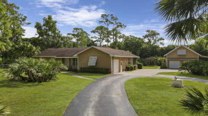 This 3 bedroom, 2.5 bath home sits on a beautiful 1.25 acre, fully fenced & gated Jupiter Farms property. The home offers a combined living-dining room, a family room opening to the back patio, a storage room and attached garage. The second structure includes a two car garage, carport and a 1,158 sq ft private entry living studio with kitchenette and bathroom. The property has a very spacious, landscaped backyard with wooden gazebo. One owner and NO HOA!
