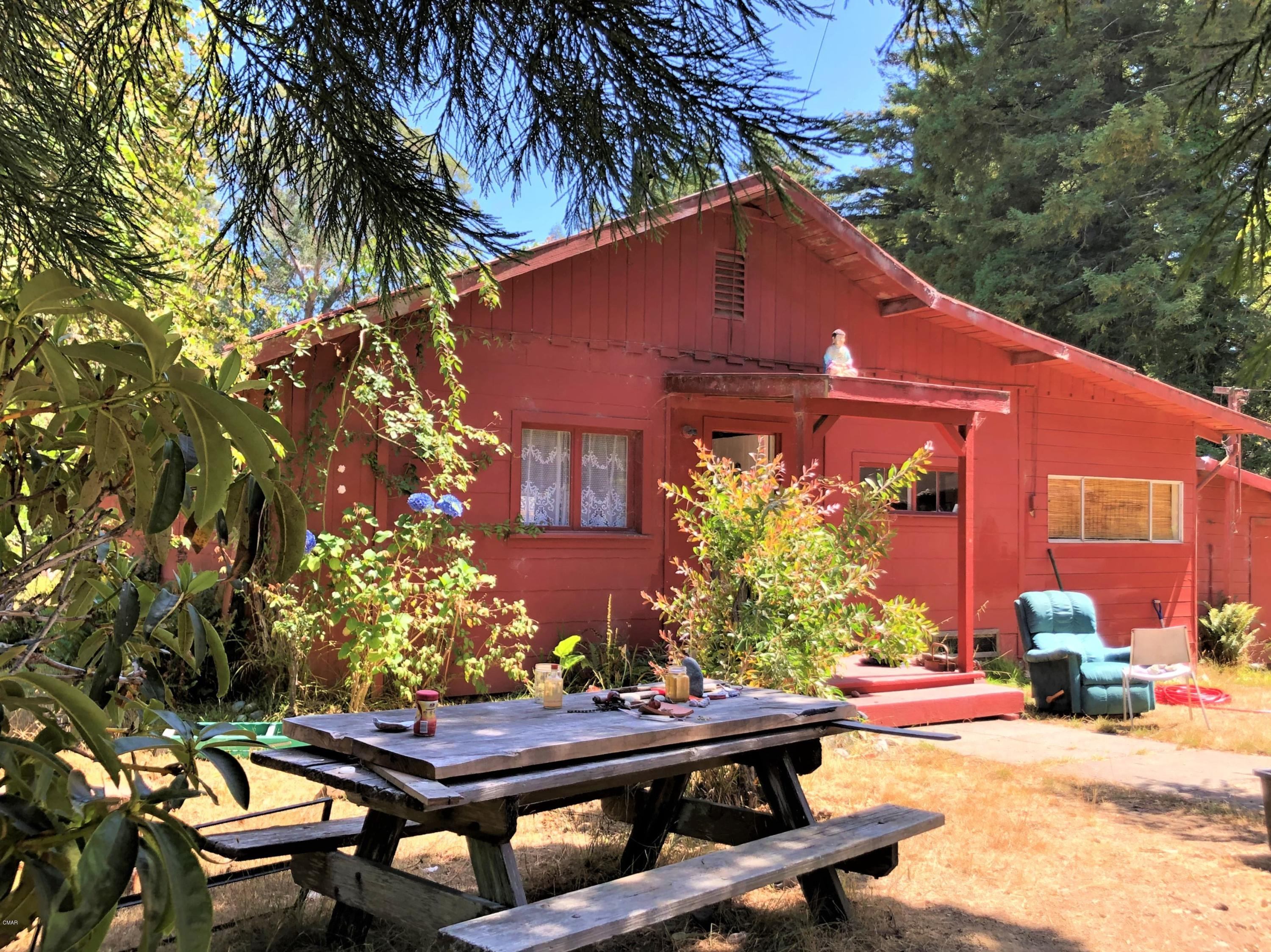 Beautiful sunbelt country land with fixer home and outbuildings. This property is ideal for gardens and animals. The acreage has a nice mix of sunny clearings and trees, including some gorgeous redwoods. There is even a seasonal stream. The well has been providing a good supply of water. The septic has been recently updated.The older house has two bedrooms, a bathroom, living room, kitchen, dining area and laundry room. Out buildings include a sheds, studio, workshop and garage. Bring tool belt and dreams.