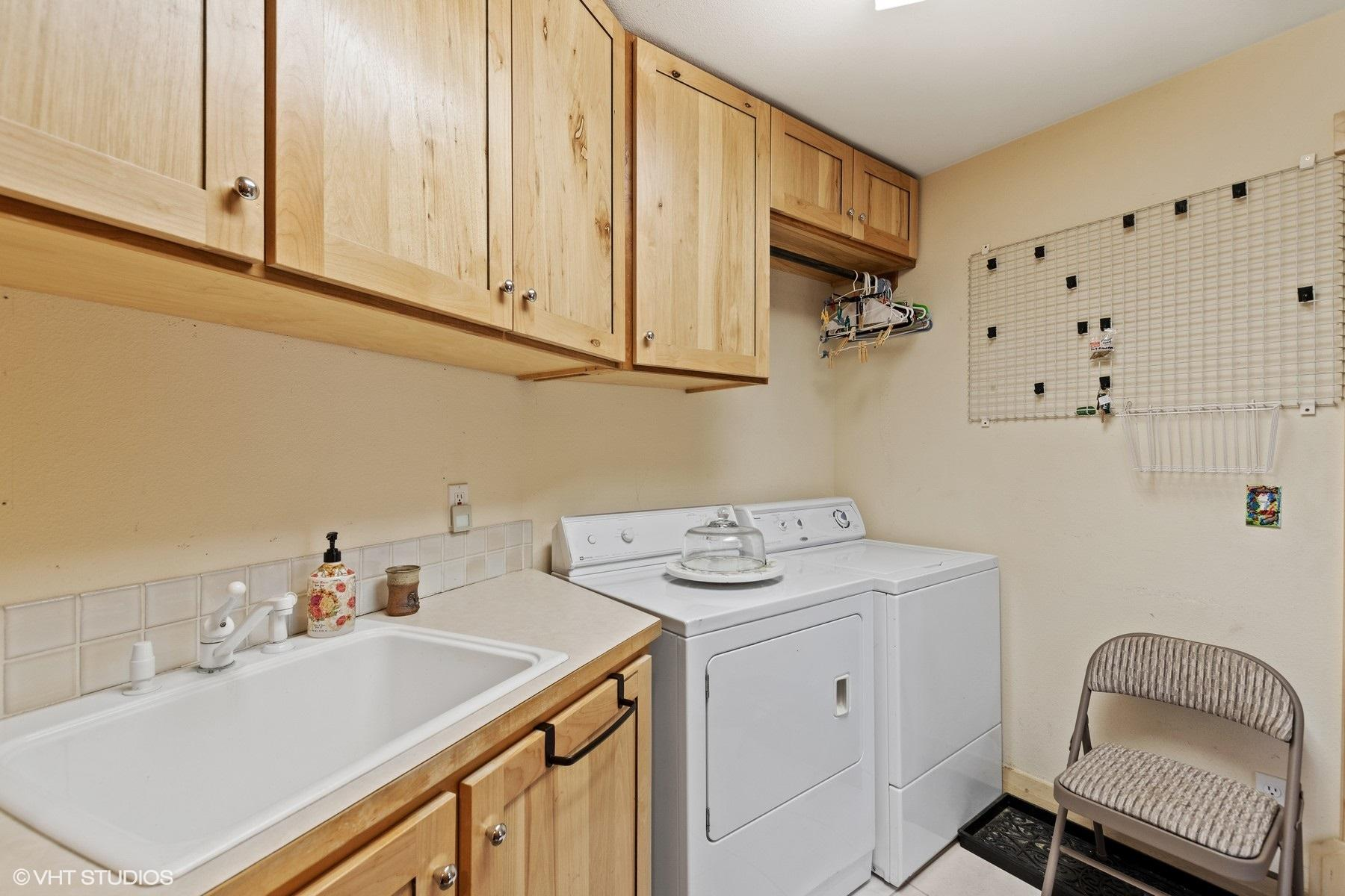 Full laundry room with cabinets and sink