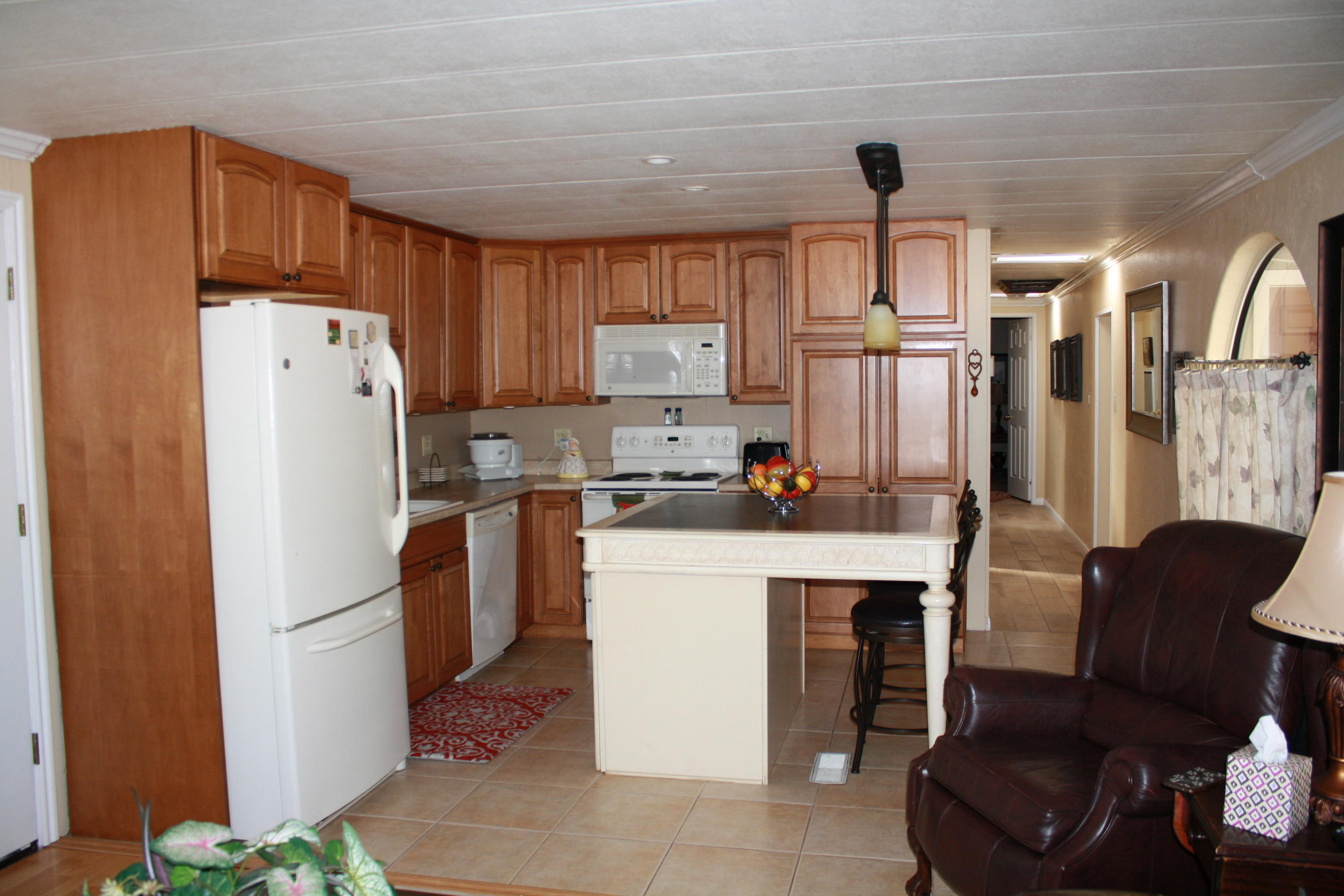 Charming manufactured home has been well taken care of. Perfect snowbird getaway or great starter home. The lot is owned with NO HOA. The yard is full of charm w/mature trees to enjoy sitting on the front deck or the backyard patio. Backyard also offers 2 large storage sheds and a workshop w/ample room for storage. Large RV Parking area.Seller is excluding washer/dryer/LG Refrigerator in shop.