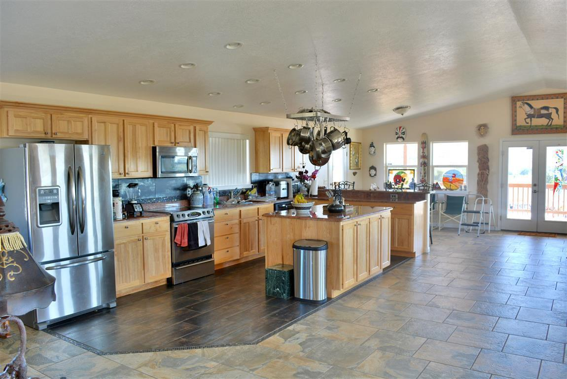 Huge Price Reduction! Custom-built home with large open floor plan and tons of upgrades. Slate and tile floors, granite, can lights, vaulted ceilings & central air. Large gourmet kitchen with island & eating bar make this home perfect for entertaining or just relaxing after a day of hiking! 1 share irrigation with some outbuildings. Great horse property on 1 Acre with corrals, shed, fencing.