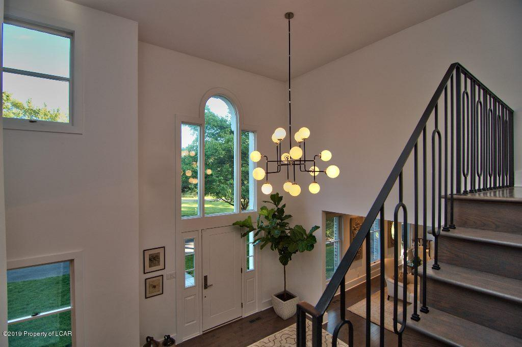 Foyer with elegant fixture and windows