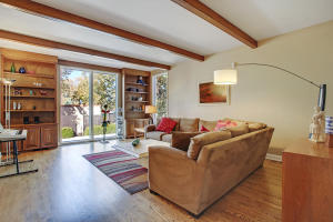 the sunny formal living room has oversized windows and gleaming hardwood floors