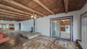 Spacious Main Living area with Custom Vigas ceilings, brick floors and beautiful Tile accents throughout this lovely adobe Casa - must see to appreciate.