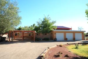 Two homes, 3 garages and 2-car carport on over half an acre of irrigated land. Backs to Village of Los Ranchos Green Space.
