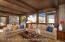 Cozy den and dining area with woodburning fireplace and expansive windows with spectacular views of Snowmass Mtn ski trails