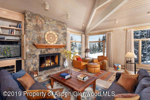 Features include stone woodburning fireplace and wood floors.