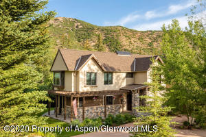 There is a 3-car attached garage which is obscured by aspen trees in this photo.