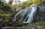 The banded falls of Fall Creek run past the Alpine house down through the property.