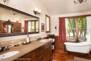 Master bath with classic free standing white bathtub