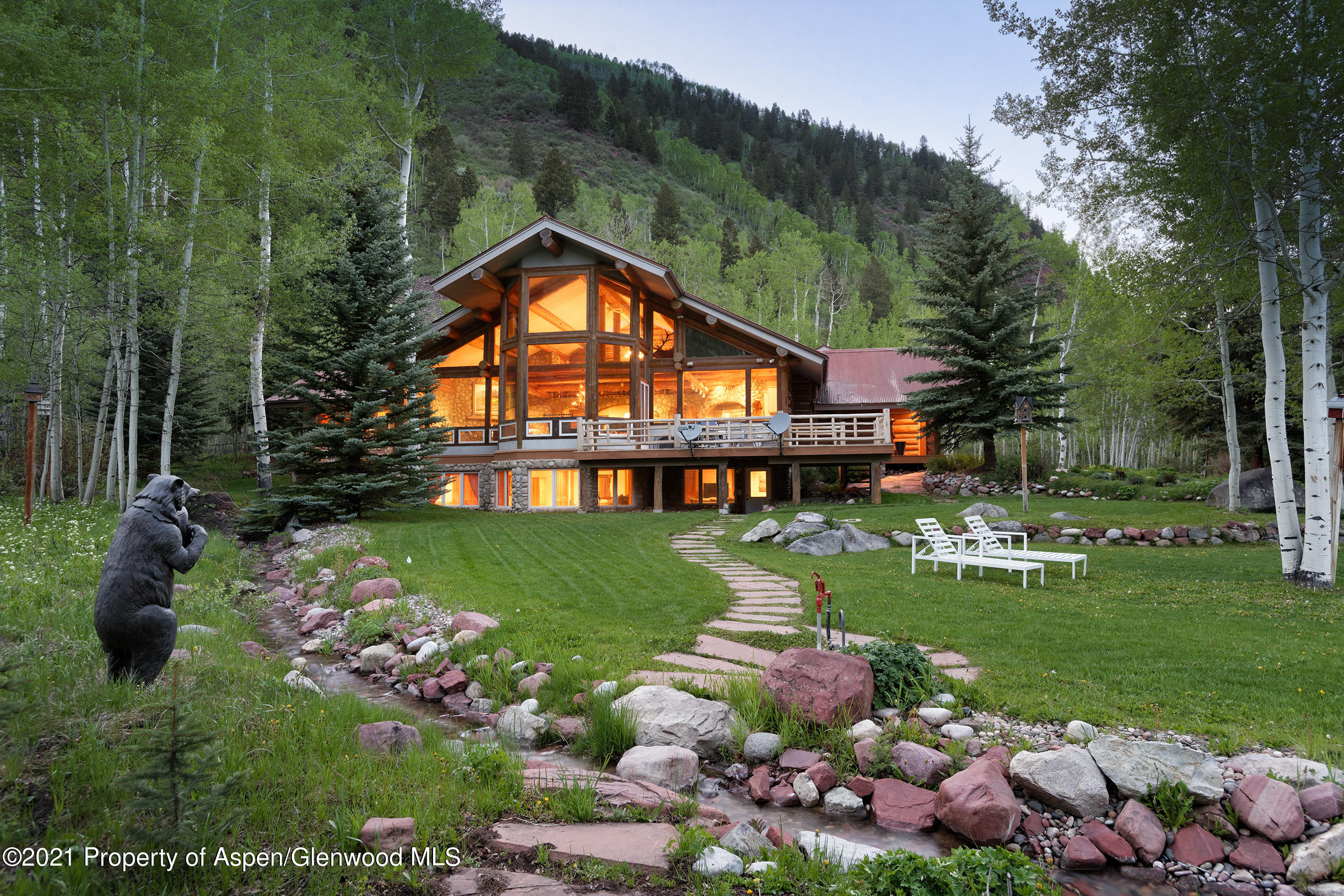 Step into this inviting 5 bedroom, 5.5 bath, mountain estate, just 10 minutes from downtown Aspen... and feel immediately at home! The spectacular Great Room is the heart of the home with its vaulted beam ceiling, multiple sitting areas, dramatic stone fireplace, dining area, gourmet kitchen, and deck overlooking your private pond. Large windows throughout brighten the traditional log home warmth. Impressive master bedroom suite includes large sitting area with huge picture windows, fabulous master bath with his and her walk-in closets, multiple vanities, separate makeup station, and rainfall shower with multiple heads, all nestled among the private aspen groves.  Separate office, home gym, 3-car oversized garage for the toys, water rights, over 3 acres of country privacy, and much more!