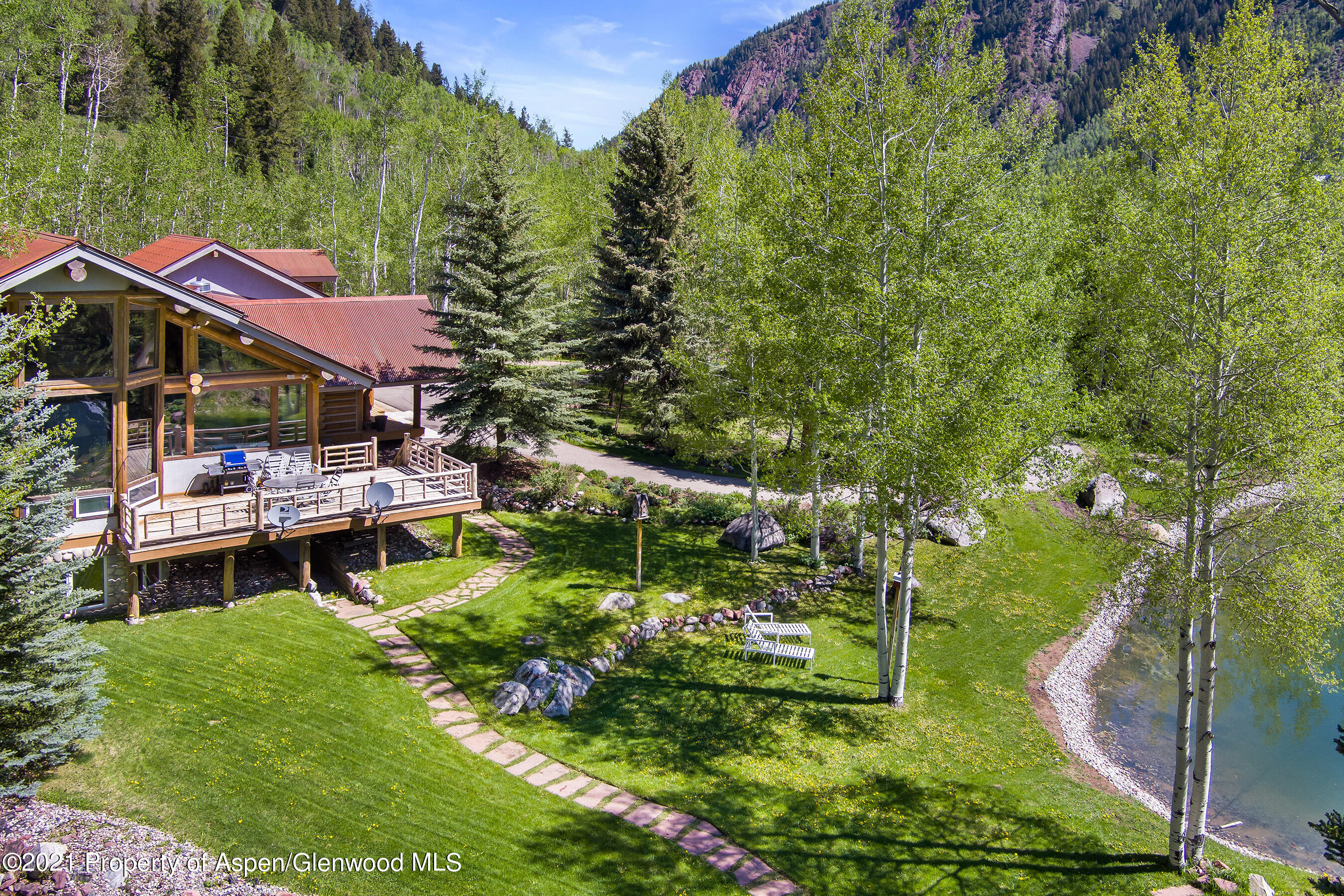 Step into this inviting 4 bedroom, 5 bath, mountain estate, just 10 minutes from downtown Aspen... and feel immediately at home! The spectacular Great Room is the heart of the home with its vaulted beam ceiling, multiple sitting areas, dramatic stone fireplace, dining area, gourmet kitchen, and deck overlooking your private pond. Large windows throughout brighten the traditional log home warmth. Impressive master bedroom suite includes large sitting area with huge picture windows, fabulous master bath with his and her walk-in closets, multiple vanities, separate makeup station, and rainfall shower with multiple heads, all nestled among the private aspen groves.  Separate office, home gym, 3-car oversized garage for the toys, water rights, over 3 acres of country privacy, and much more!