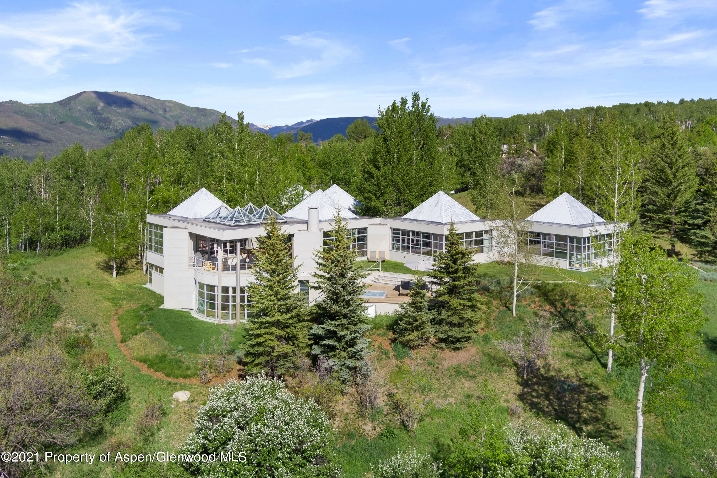 Welcome to a home like no other: a compelling 7,300+ sq. ft. estate among the green rolling hills in the Owl Creek Valley. Sited on a premium 4 acre lot, every room in the home is designed to showcase the 360 degree views of the surrounding mountains and ski slopes. Entertain in several outdoor spaces this summer on the covered deck, patio or lush green lawns. Designed by visionary and acclaimed architect Steve Haas, the modern geometric architecture is an innovative use of steel, glass and space. Custom-designed furnishings complement every room. With several dynamic living areas, a game room and four en-suite bedrooms, there is abundant space to host guests, while enjoying a sophisticated main floor master suite and den. All 4 Aspen and Snowmass ski areas are just minutes away. This property provides the privacy and splendor of the Colorado outdoors and close proximity to all that Aspen has to offer. The Aspen airport is just 5 minutes away; downtown Aspen is a quick 10 minutes drive into town.
