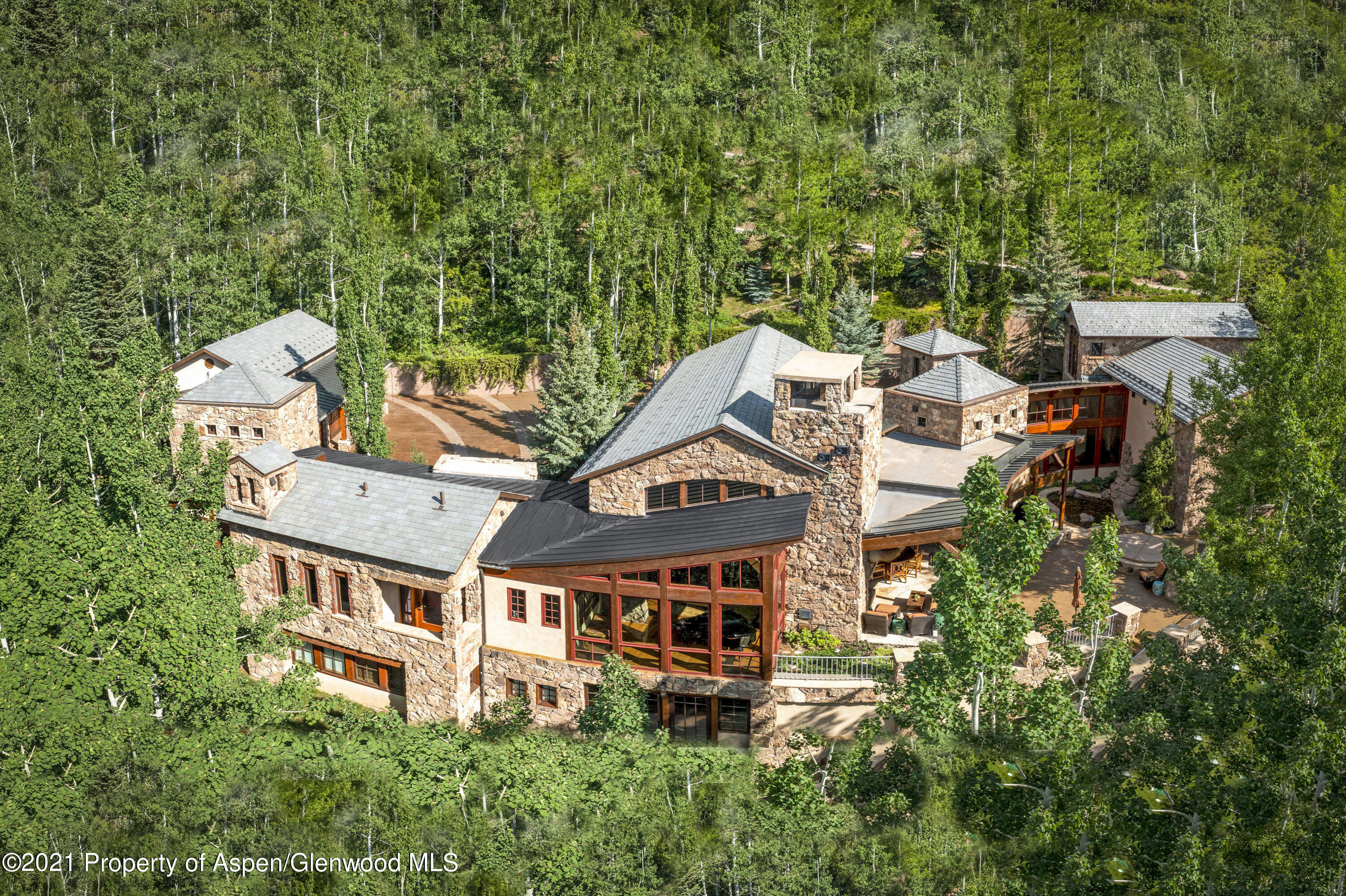 Located at the terminus of secluded Falcon Road in Five Trees, this ski in/ ski out, 5 bedroom, 9 bath estate embodies architectural artistry, Colorado majesty and ultimate privacy. This 8,983 SF home has interiors of thoughtful finishes, including dramatic stone fireplaces and archways, walls of windows framing mountain views, ash wood floors and soaring ceilings with wooden beam trusses, the home captures a Tuscan aesthetic with materials that are indigenous to Colorado, creating a magnificent synergy.A stand-out feature of the home on 1.4 acres is the stunning elevated outdoor patio complete with a cascading waterfall, oversized stone hearth, spa and northwestern views looking up the Roaring Fork Valley and west towards Baldy Peak and the Willow Creek Valley. Located off the great room and kitchen, the beautiful space welcomes large scale al fresco entertaining or intimate dinners and offers both sunny and shaded areas.  Walls of glass flood the interiors with natural light and vistas of rugged peaks. The open floor plan segues seamlessly between the formal living room with its dramatic stone fireplace, the formal dining room that easily seats 12, and the chef's kitchen. The kitchen features top-of-the-line appliances plus an oversized center island with stools for meals on the go as well as an alcove for informal family gatherings.  The 5 en suite bedrooms serve as a haven for any family member or guest. The main level primary suite is an oasis of calm with mountain views, fireplace and a bathroom with a soaking tub and oversized shower. The other 4 bedrooms are spread throughout the home on various levels, lower two bedrooms have elevator service.  The home is further appointed with a 1,000-plus-bottle stone wine cellar and tasting table, a glass alcove that currently houses a grand piano, a wet bar, a club room and an office with a private entrance. The lower walk-out level also features a bonus room that could be used for a kids playroom or workout room. The 