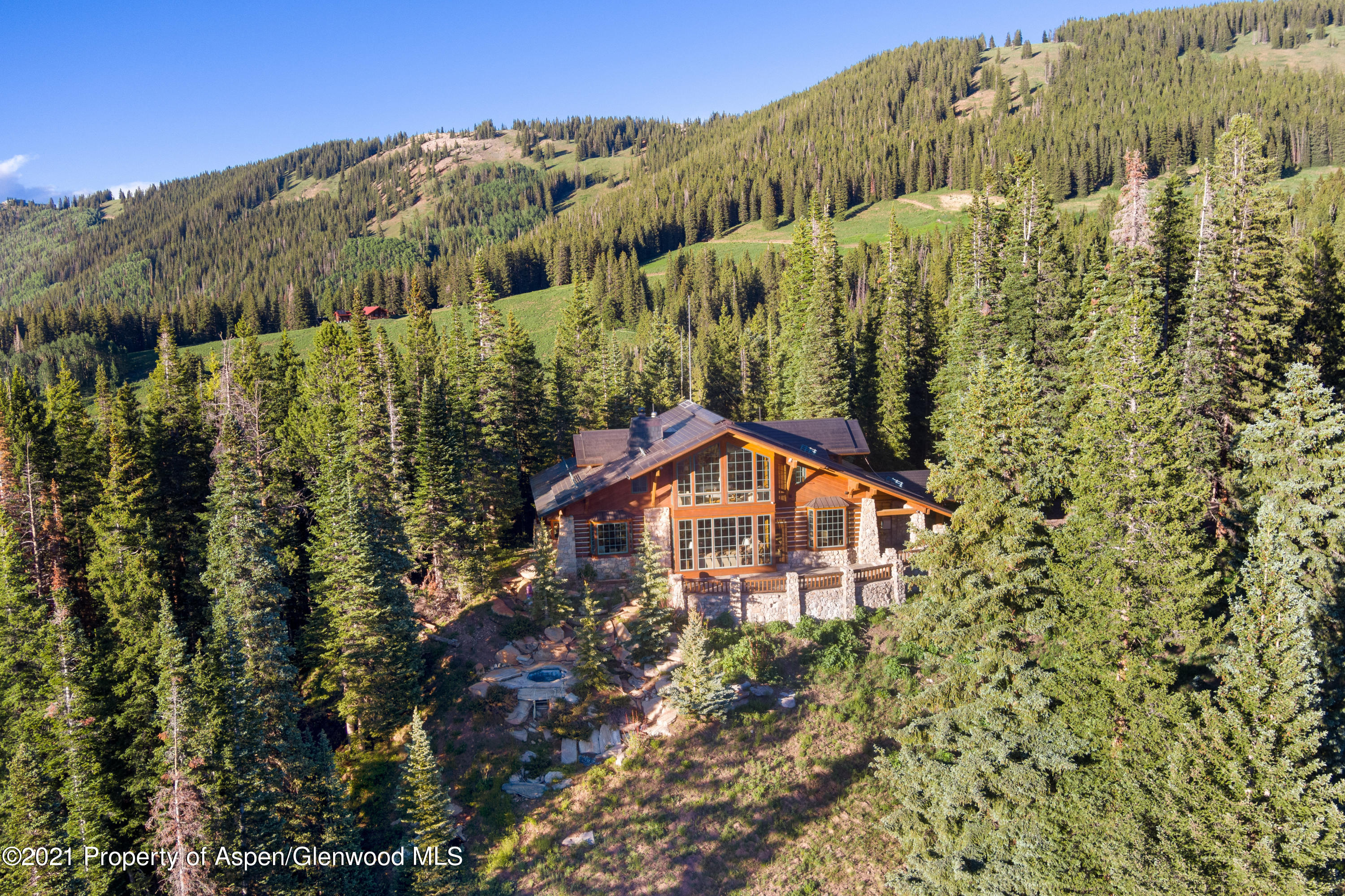 When you dream about living in the mountains, this is what it looks like! This quintessential Aspen Ski Chalet is situated on 48 acres on a private ridge on the backside of Aspen Mountain at the confluence of Little Annie's Basin and Midnight Mine Road. Ski home from Ajax or ski tour out your front door. Timeless woodworking and custom craftsmanship by Rutger's Construction distinguishes the 3,461 sq.ft. main house with four ensuite bedrooms plus powder room, gym and library, den. Floor to ceiling windows in the great room and upper-level master bedroom capture perfectly framed views. A two-bedroom guest house equipped with kitchen and wood stove is located below the main house. This is the ultimate Aspen Mountain ski retreat with forever views and surrounded by White River National Forest When you dream about living in the mountains, this is what it looks like! This quintessential Aspen Ski Chalet is situated on 48 acres on a private ridge on the backside of Aspen Mountain at the confluence of Little Annie's Basin and Midnight Mine Road. Ski home from the Sundeck and Silver Queen Gondola or ski tour Little Annie's out your front door. Timeless woodworking and custom craftsmanship designed by Wayne Paulson and built by Rutger's Construction distinguishes the 3,461 sq. ft. irreplaceable main house with four en suite bedrooms plus powder room, gym and library, den. Floor to ceiling, south facing windows in the great room and upper-level master bedroom capture perfectly framed views of Five Fingers, Conundrum Valley, Highlands Bowl and Ski Hayden. The open great room is centered around a Colorado moss rock wood-burning fireplace that warms the home. Pine flooring and radiant heat are throughout. A library, den media room with flatscreen and built-ins for your favorite books is ideal for post ski movies or a cozy read. A main level guest master suite with vaulted cupola spa bathroom includes separate marble shower, dual vanities and a soaking tub that looks out over the