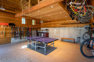 Garage has been tiled and is designed for ping pong and other play when cars are pulled out. Enormous amount of storage for bikes and skis.