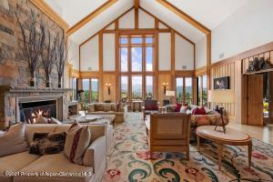 The great room boasts 30-feet vaulted ceilings and floor-to-ceiling windows to capture the exceptional mountain views.