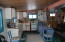 Kitchen area with propane stove and refrigerator and hand pump well!
