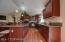 Granite kitchen counters and rich cabinets and flooring are noticeable features.