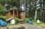 This cozy tiny home features a large, covered porch boarded by perennial gardens. The front yard also features several raised garden beds. An outhouse is located adjacent to the cabin.