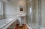 Main bath room with a large window, soaking tub, tiled shower, ease to clean, pocket door