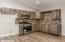 Kitchen: Stainless Steel Appliances, Laminate Flooring, Tile back-splash