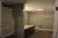 Upstairs hall bath offers deep soaking tub/shower combo and storage shelves.