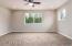 Bedroom with lit double door closets, ceiling fan