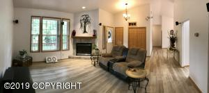 Inviting living room with gas fireplace and vaulted ceiling...carpet has been replaced with beautiful laminate flooring throughout living, kitchen, halls, and dining area!