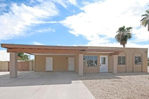 Easy care desert landscaping in the front yard with tall palm trees, a two car carport and extra side slab for additional parking. RV gate, covered back patio and block wall fencing. Near shopping, restaurants and Valley freeways.