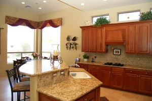 Large kitchen island with beautiful Fiarito granite. Solid cherry cabinets include extensive pull outs and fine detailing, like the rope accent molding and interesting hood for gas cooktop.
