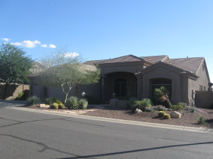 North facing home with easy care desert landscape & extra exterior lighting.